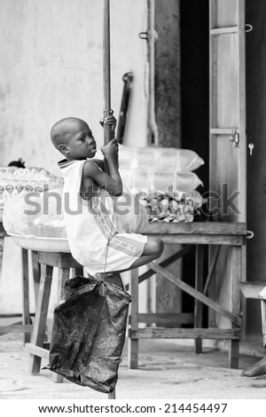 PORTO-NOVO, BENIN - MAR 10, 2012: Unidentified Beninese boy in a basketball shirt plays at the porch. People of Benin suffer of poverty due to the difficult economic situation