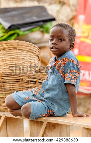 PORTO-NOVO, BENIN - MAR 10, 2012: Unidentified Beninese boy walks on the wooden bench. People of Benin suffer of poverty due to the difficult economic situation