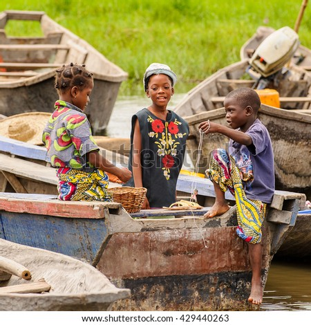 PORTO-NOVO, BENIN - MAR 9, 2012: Unidentified Beninese children play in a fishing boat. People of Benin suffer of poverty due to the difficult economic situation.