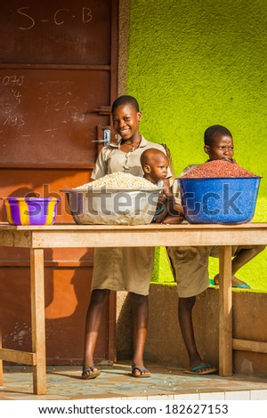 PORTO-NOVO, BENIN - MAR 9, 2012: Unidentified Beninese girl sells cereals with her children. People of Benin suffer of poverty due to the difficult economic situation.