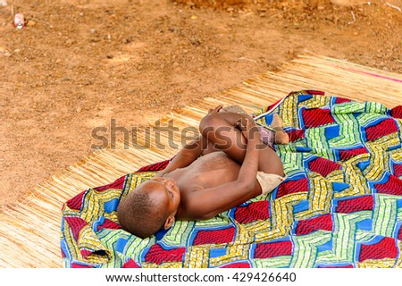 PORTO-NOVO, BENIN - MAR 8, 2012: Unidentified Beninese little boy plays on the ground. People of Benin suffer of poverty due to the difficult economic situation.