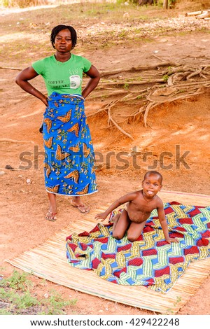 PORTO-NOVO, BENIN - MAR 8, 2012: Unidentified Beninese little boy plays on the ground with his mother. People of Benin suffer of poverty due to the difficult economic situation.