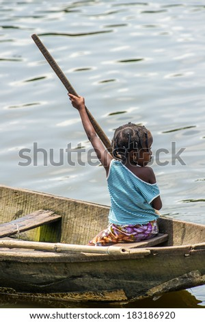 PORTO-NOVO, BENIN - MAR 9, 2012: Unidentified Beninese little girl rows a wooden boat. People of Benin suffer of poverty due to the difficult economic situation.