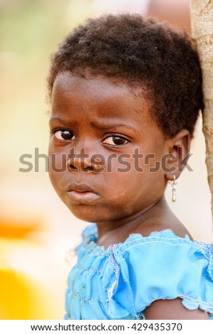 PORTO-NOVO, BENIN - MAR 8, 2012: Unidentified Beninese little sad girl near the tree. People of Benin suffer of poverty due to the difficult economic situation.