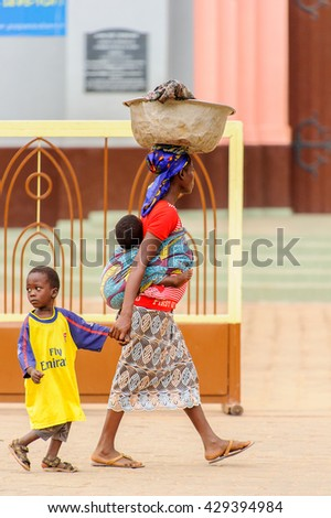 PORTO-NOVO, BENIN - MAR 10, 2012: Unidentified Beninese woman a son and a little child on a back. People of Benin suffer of poverty due to the difficult economic situation