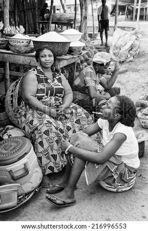 PORTO-NOVO, BENIN - MAR 8, 2012: Unidentified Beninese woman and her daughter work at market. People of Benin suffer of poverty due to the difficult economic situation.