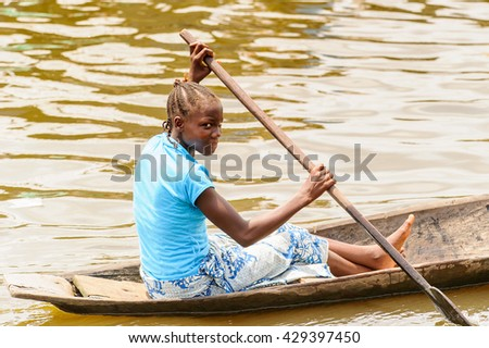 PORTO-NOVO, BENIN - MAR 9, 2012: Unidentified Beninese woman in a blue shirt rows a wooden boat. People of Benin suffer of poverty due to the difficult economic situation.