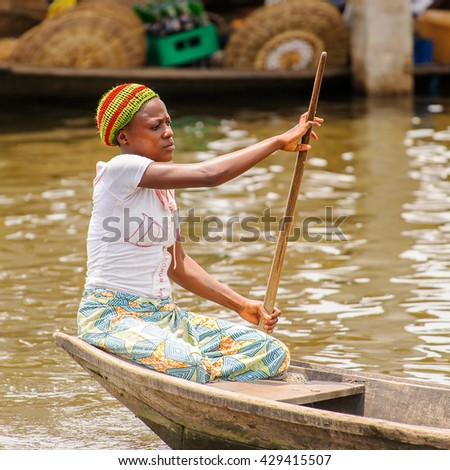 PORTO-NOVO, BENIN - MAR 9, 2012: Unidentified Beninese woman in a hat rows a wooden boat. People of Benin suffer of poverty due to the difficult economic situation.