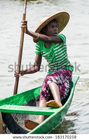 PORTO-NOVO, BENIN - MAR 9, 2012: Unidentified Beninese woman raws a green wooden boat. People of Benin suffer of poverty due to the difficult economic situation.