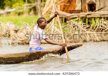 PORTO-NOVO, BENIN - MAR 9, 2012: Unidentified Beninese woman rows a wooden boat.People of Benin suffer of poverty due to the difficult economic situation