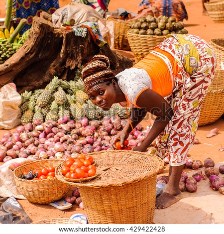 PORTO-NOVO, BENIN - MAR 9, 2012: Unidentified Beninese woman sells garlic and tomatoes at the local market. People of Benin suffer of poverty due to the difficult economic situation.