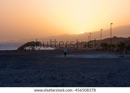 PORTO NOVO, CAPE VERDE - DECEMBER 09, 2015: Amazing sunset evening at the beach of Santo Antao Island. People walking and watching the sun - stock photo