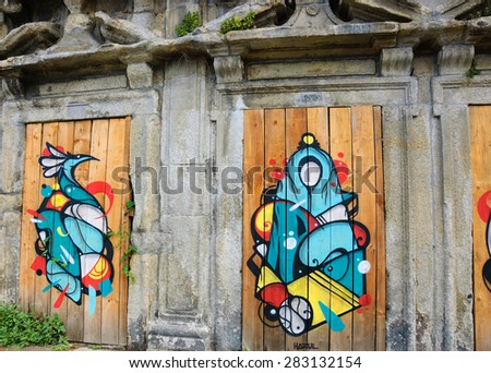 PORTO, PORTUGAL - APRIL 26, 2015: Virgin Mary and bird by graffiti artist Hazul Luzah. Hazul incorporates the Virgin Mary image in many of his works which based on the decorative calligraphic forms. - stock photo