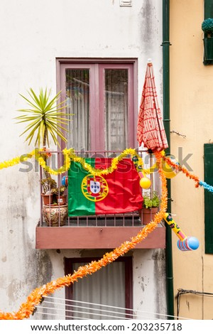 PORTO, PORTUGAL - JUN 21, 2014:  Balcony with the national flag in Porto, Portugal. Porto is the second largest city in Portugal and it was called the European Culture Capital in 2001