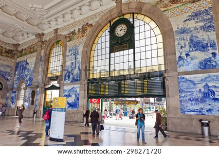 PORTO, PORTUGAL - JUNE 20, 2013: Painted ceramic tileworks (Azulejos) on the walls of Main hall of Sao Bento Railway Station in Porto. The building of station is a popular tourist attraction of Europe - stock photo