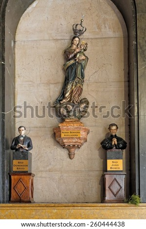 Porto, Portugal - March 4, 2015: Small side niche of the church Santo Antonio dos Congregados with the images of Our Lady Help of Christians, Saint Dominic Savio and St. John Bosco. High ISO photo. - stock photo