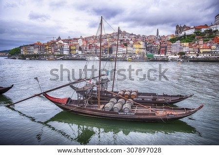 PORTO, PORTUGAL - MAY 2, 2015: Two boats filled with pipes, or barrels, of port wine float on the Douro River with the city of Porto behind. The boats show the names of port houses as floating ads.