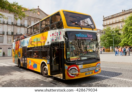 PORTO, PORTUGAL - MAY 26, 2016: Yellow Bus on Liberdade Square in the historical center of Porto, Portugal (UNESCO site). Yellow Bus provides sightseeing tours around main attraction of the city