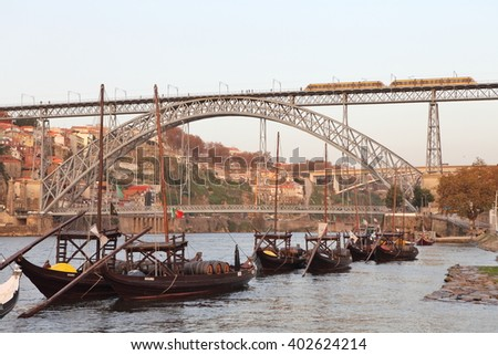 PORTO, PORTUGAL - November 24, 2014: traditional boats with wine barrels with the metro train on Dom Luis bridge and Porto city in the background - stock photo