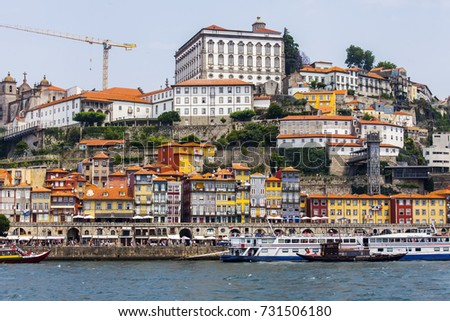 PORTO, PORTUGAL, on June 17, 2017. The sun lights the embankment on the opposite bank of the river of Duero. People and cars move on the embankment. Authentic boats are moored at pier