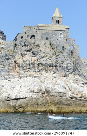 Portovenere, Italy - 7 July 2015: people navigating their boat in front of the old church on a rocky coastal outcrop at Portovenere, Italy
