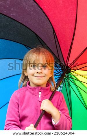 Portrain of little girl wearing pink fleece jacket holding colorful umbrella - stock photo