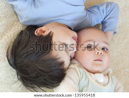 Portrait a baby and a toddler child lying on a fur sheet, cuddling, top view.