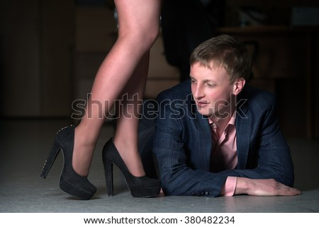 portrait a man lying on the floor at the woman's feet - stock photo