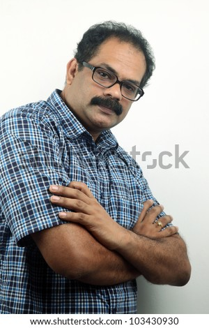 Portrait a seriously looking Indian male with folded hands - stock photo