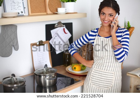 Portrait a smiling woman text messaging of vegetables in kitchen at home