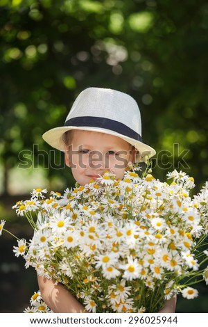 Portrait adorable boy in a hat with big white bouquet of camomiles  - stock photo