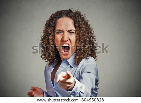 Portrait angry young woman pointing finger at camera screaming isolated on grey wall background - stock photo