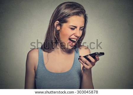 Portrait angry young woman screaming on mobile phone isolated on gray wall background. Negative human emotions feelings - stock photo