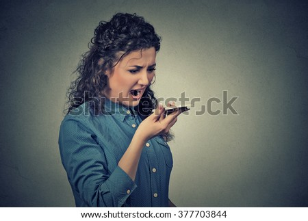 Portrait angry young woman screaming on mobile phone standing isolated on gray wall background. Negative human emotions feelings - stock photo