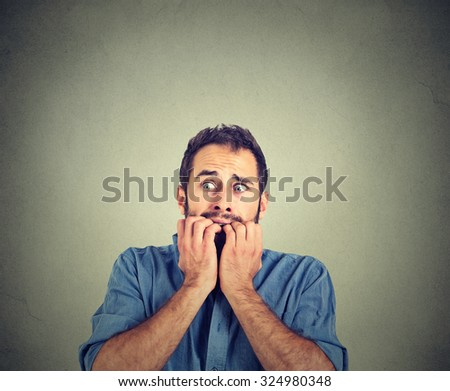 Portrait anxious young man biting his nails fingers freaking out  - stock photo