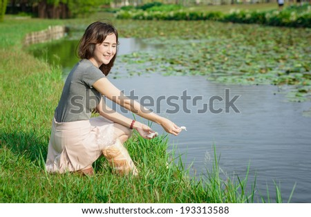 portrait asia Young girl happy and feeding for fish in old lake natural at outdoor garden