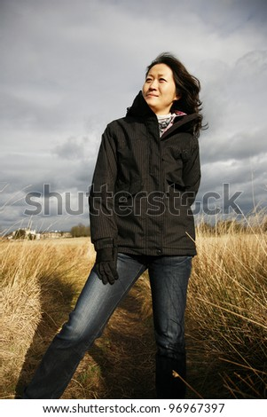 Portrait asian woman, looking off into distance in the field