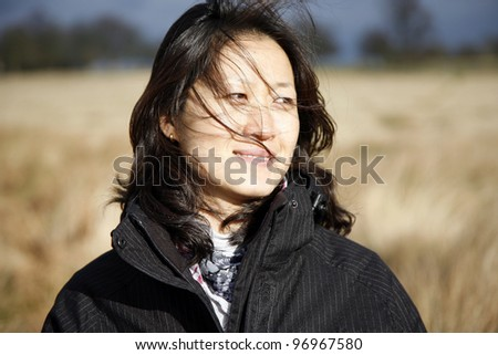 Portrait asian woman, looking off into distance in the field - stock photo