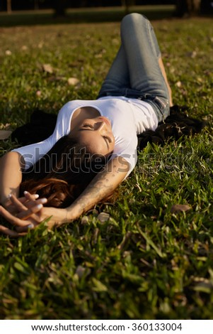 Portrait asian woman luying on the grass in park - stock photo