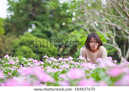 Portrait Asian woman standing. Blue flowers arranged in lotus-shape in the park. She was relax