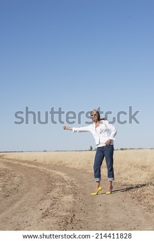 Portrait attractive and confident attractive mature woman, hitchhiking in rural country , smiling, happy, thumb up, with horizon and blue sky as background and copy space.