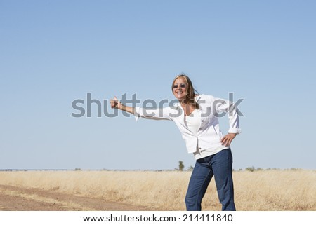 Portrait attractive and confident attractive mature woman traveling, hitchhiking in rural country , smiling, happy, thumb up, with horizon and blue sky as background and copy space.