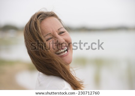 Portrait attractive confident mature woman outdoor looking happy and joyful, wind blowing hair into face, with bright blurred background and copy space. - stock photo