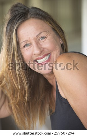 Portrait attractive confident mature woman smiling friendly happy relaxed, playful seductive with hand in long brunette hair, blurred background. - stock photo
