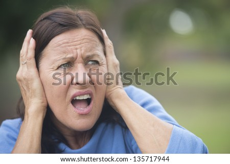 Portrait attractive mature woman covering frustrated, angry or in anxiety her ears with hands, stressed shocked, isolated with blurred outdoor background. - stock photo