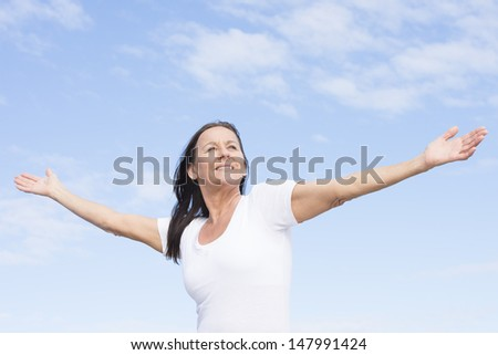 Portrait attractive mature woman, happy, friendly, positive, successful, enjoying active retirement, with arms up, isolated outdoor with blue sky as background and copy space. - stock photo