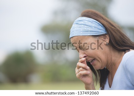 Portrait attractive mature woman outdoor suffering from seasonal hayfever or cold or flu, sneezing, with hand on nose, closed eyes, with blurred background and copy space. - stock photo