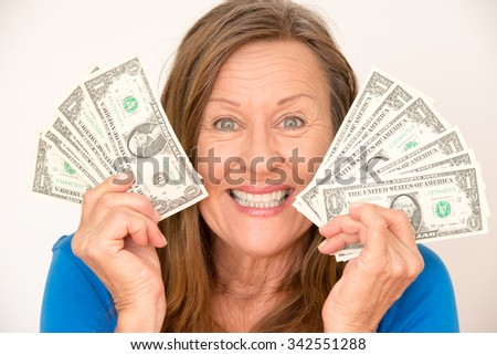 Portrait attractive mature woman presenting happy joyful relaxed us dollar notes, isolated, bright background.