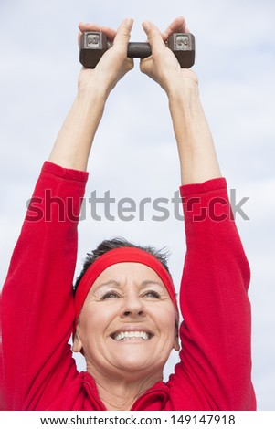 Portrait attractive mature woman showing active retirement, exercising with weights arms up outdoor, positive, confident, energetic, focused, with cloudy sky as background and copy space. - stock photo