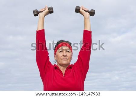 Portrait attractive mature woman showing active retirement exercising